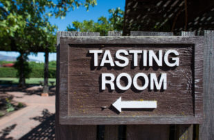 Directional sign pointing to wine tasting room in Napa, California.