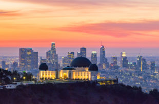 Los Angeles skyline at dawn with Griffith Park Observatory in the foreground