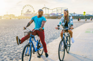 couple having fun riding bikes together at santa monica california near sunset